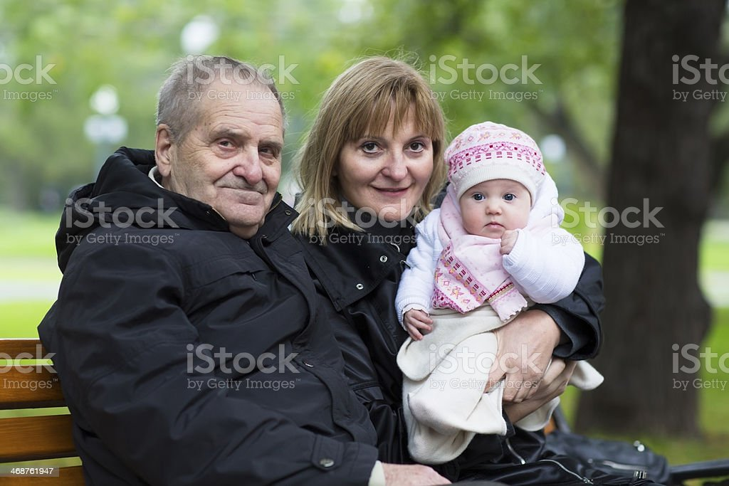 Great-grandfather, grandmother and little baby girl in the park royalty-free stock photo