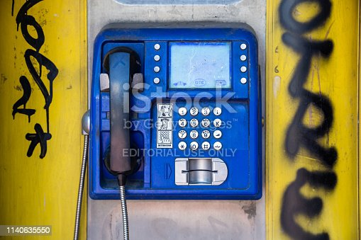 March 31st, 2019, Greece Athens. Public card phone, blue color on yellow color wall with graffiti, city center
