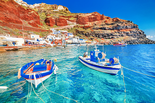 Greece. Breathtaking beautiful landscape of two fishing boats anchored to quay in fascinating blue water at the amazing old port panorama in Oia Ia village on Santorini Greek island in Aegean sea.