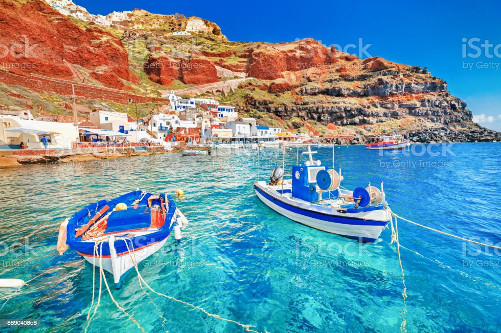 Greece. Breathtaking beautiful landscape of two fishing boats anchored to quay in fascinating blue water at the amazing old port panorama in Oia Ia village on Santorini Greek island in Aegean sea. stock photo