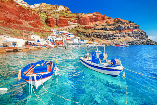greece. breathtaking beautiful landscape of two fishing boats anchored to quay in fascinating blue water at the amazing old port panorama in oia ia village on santorini greek island in aegean sea. - cyclady zdjęcia i obrazy z banku zdjęć
