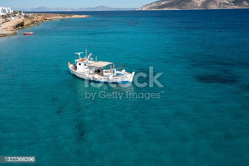 istock Greece, Cyclades. Aerial drone view of a fishing boat on turquoise color sea water 1322366396