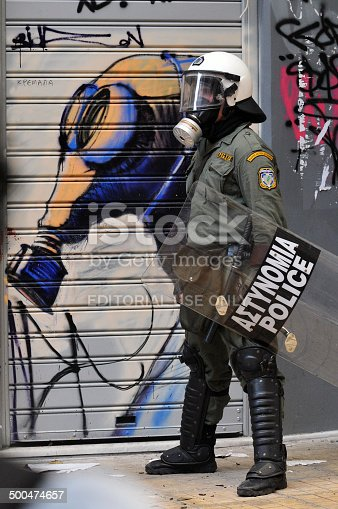 Athens, Greece - December 07, 2008. Riot police officer wearing a gas mask in front of graffiti of a gas mask, during clashes in Athens, December 07, 2008.