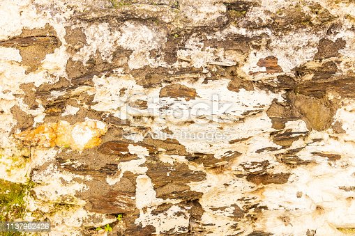 Greece, Kea island. Tzia capital city, Ioulis traditional architecture, stone wall facade, painted and faded background, closeup view