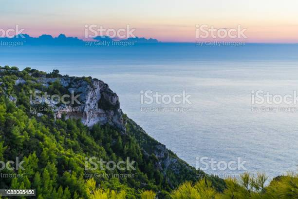 Photo of Greece, Zakynthos, Endless silent blue ocean behind green tree covered chalk cliff in evening twilight
