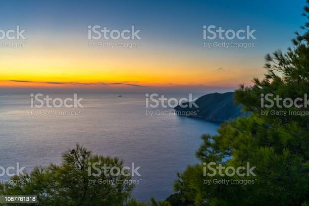 Photo of Greece, Zakynthos, Endless silent ocean and cliff behind green trees in blue hour