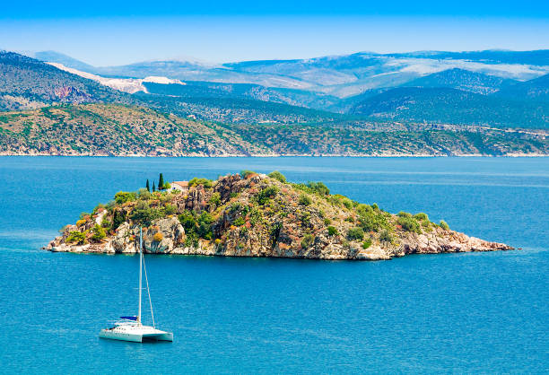 Greece,Peloponesse,Tolo town near Nafplion city. View of the sea with a small island and a white catamaran stock photo