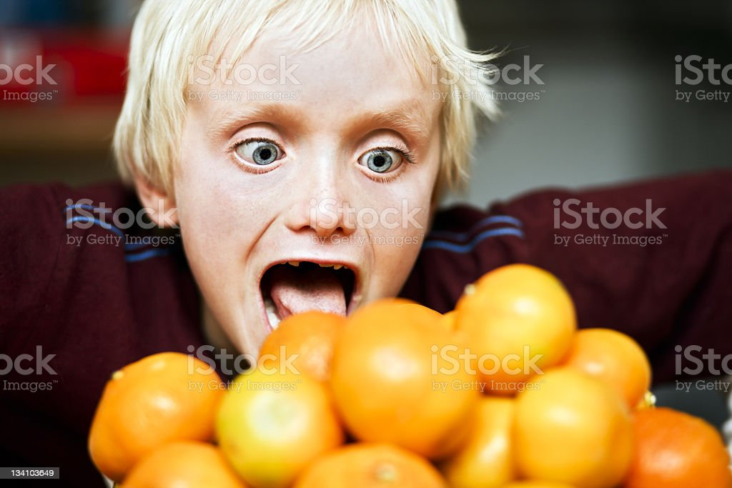 Greed! Little boy lunges at pile of delicious citrus fruit. stock photo