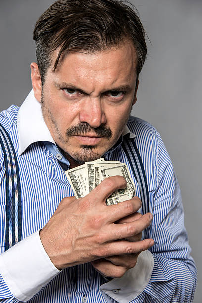 Greed Mid adult man holding a bunch of one hundred dollars bills on gray background miserly stock pictures, royalty-free photos & images