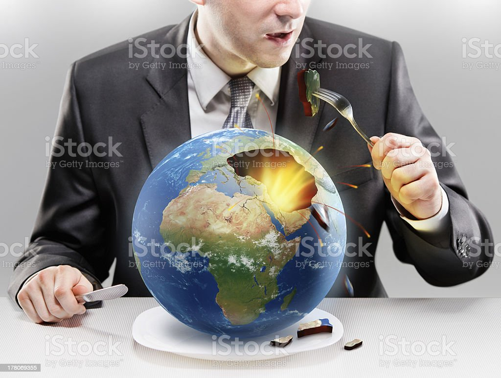 Greedy businessman eating planet Earth stock photo