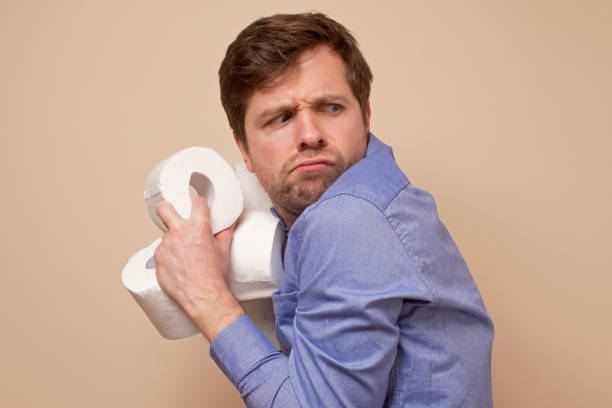 Greedy caucasian man holding several rolls of toiler paper on his hand hiding it stock photo