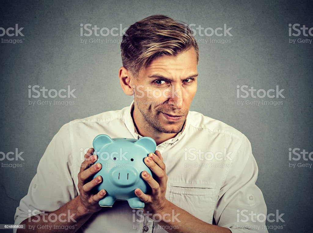 greedy stingy business man holding piggy bank stock photo