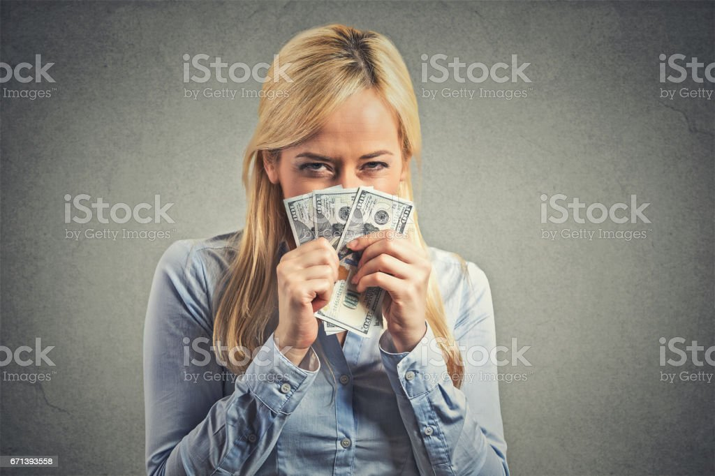 greedy young corporate employee, woman, holding dollar banknotes tight stock photo