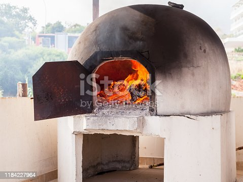 Traditional Greek and Cyprus kleftiko oven with burning fire inside