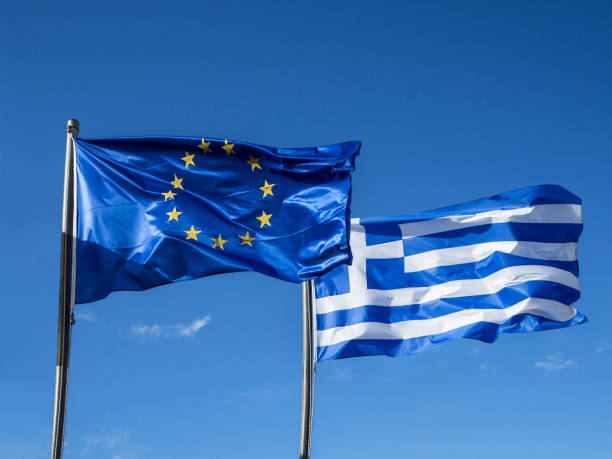 greek and european union flags waving in blue sky - grecia stato foto e immagini stock