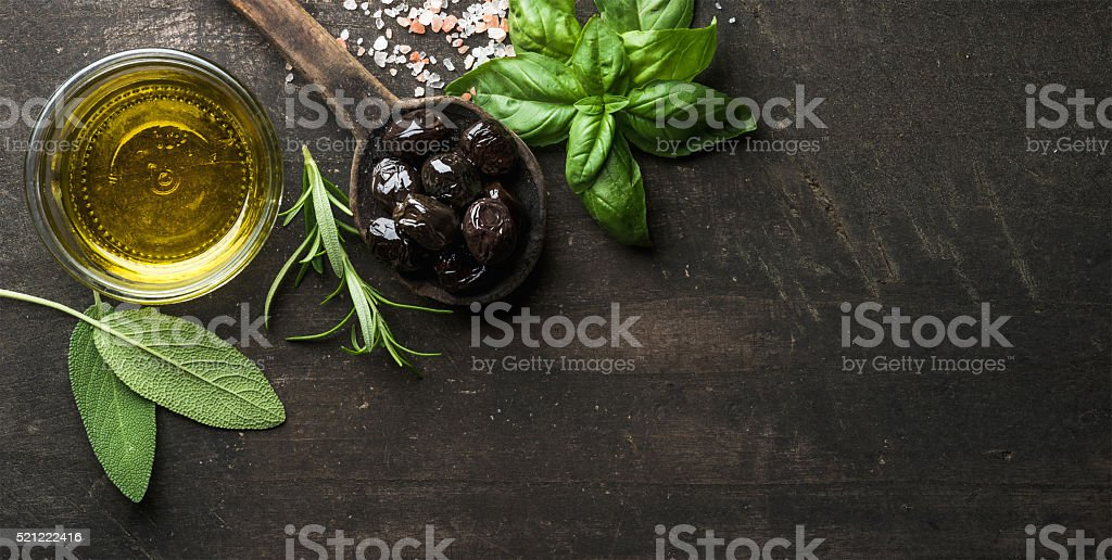 Greek black olives, fresh herbs and oil on dark rustic stock photo