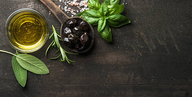 greek black olives, fresh herbs and oil on dark rustic - mediterranean culture stock photos and pictures