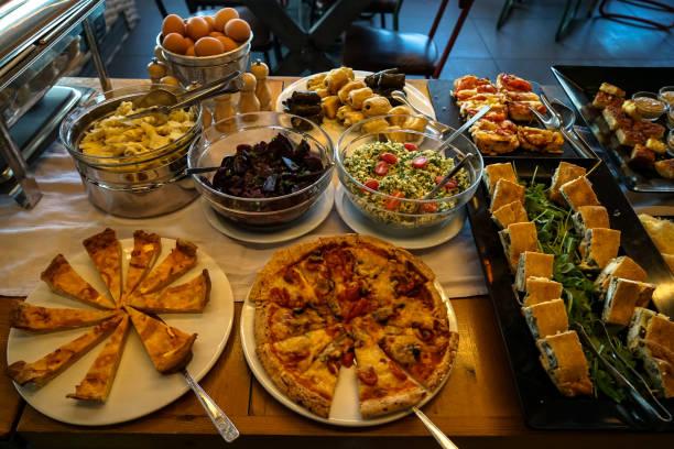 griechisches frühstück buffet-tisch voll mit sorten von pizza, kuchen, nudeln, rote beete, couscous salate, gekochten eiern, lokale gerichte, etc.. - griechischer couscous salat stock-fotos und bilder
