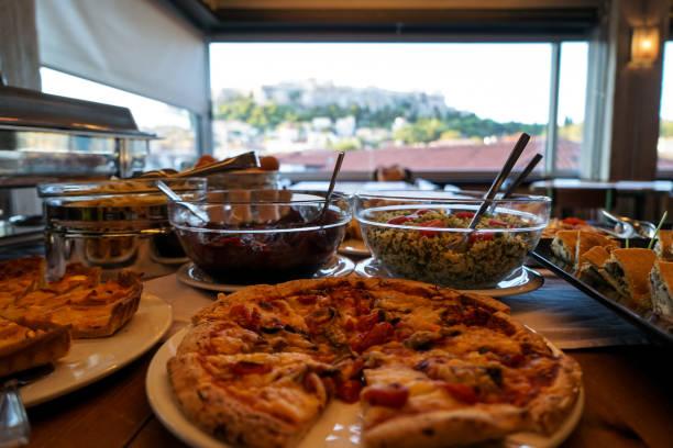 griechisches frühstück buffet-tisch voll mit sorten von pizza, kuchen, nudeln, rote beete, couscous salate, gekochten eiern, lokale gerichte, etc. mit pizza vorder- und blick auf die akropolis aus der ferne - griechischer couscous salat stock-fotos und bilder