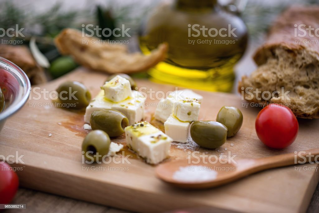 Greek cheese feta with virgin olive oil, green olives and fresh vegetables royalty-free stock photo