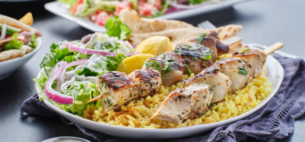 greek chicken souvlaki platter with pita bread, salad and rice stock photo