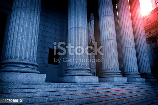 The sun peaks out from above a courthouse as red and blue tones envelope the Greek columns of the portico.