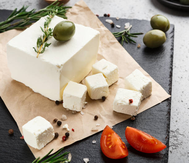 Greek cuisine concept Block of feta cheese, olives, herbs and spicies on board over concrete background. Greek cuisine concept feta cheese stock pictures, royalty-free photos & images