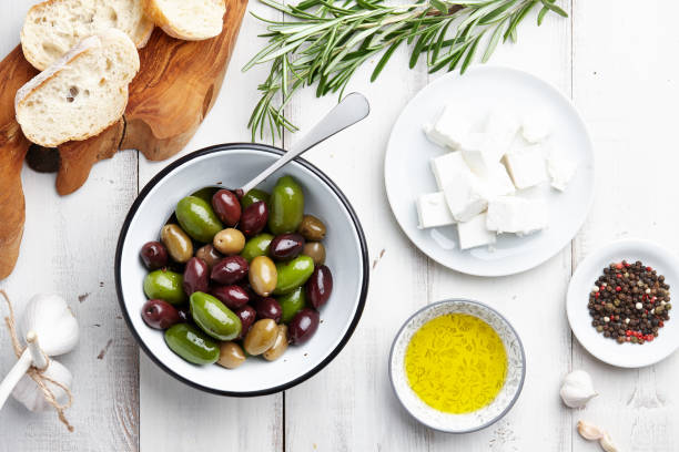 Greek cuisine ingredients Ciabatta bread, fresh olives, feta cheese, rosemary twigs, garlic, peppercorns and olive oil on white wooden background feta cheese stock pictures, royalty-free photos & images