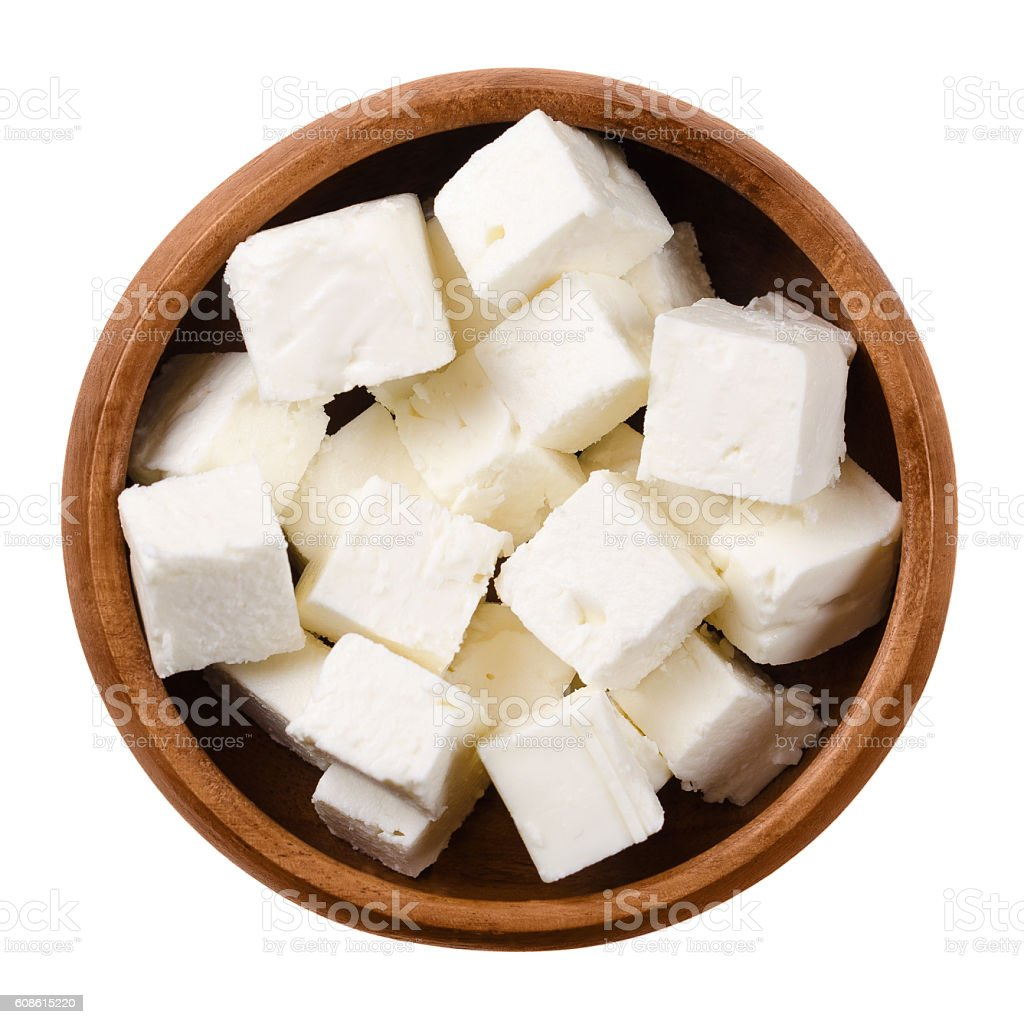 Greek Feta cheese cubes in wooden bowl over white stock photo