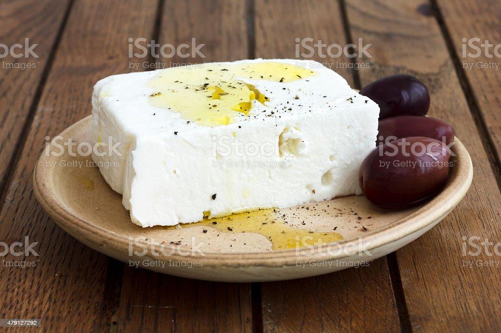 Greek feta cheese, oil, kalamata olives on rustic plate board. stock photo