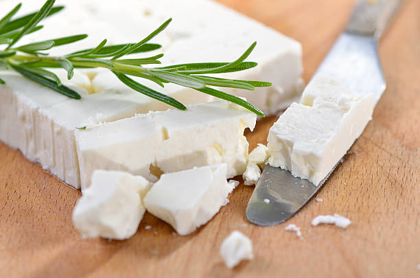 Greek feta cheese Typical Greek feta cheese made of goat milk on a wooden cutting board with a knife feta cheese stock pictures, royalty-free photos & images