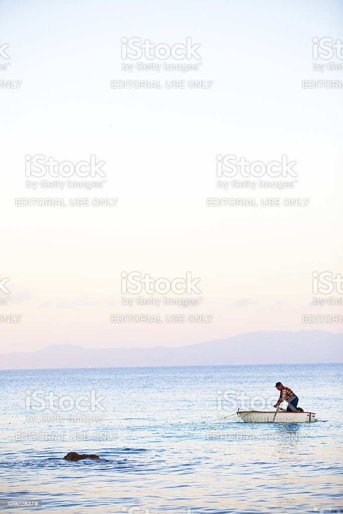 Greek fisherman rowing his boat out to set the nets royalty-free stock photo