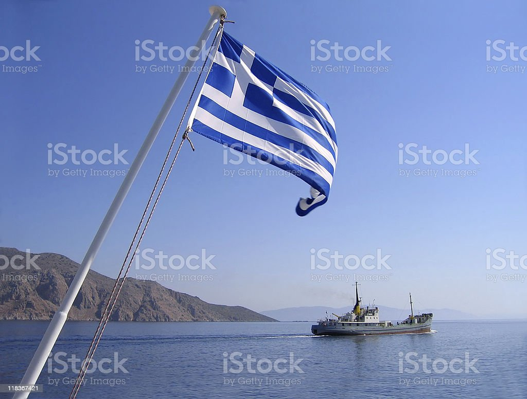Greek flag blowing in the wind at sea stock photo