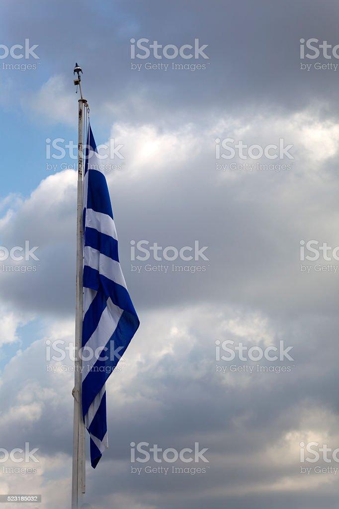 Greek flag on a flagpole against dark clouds stock photo