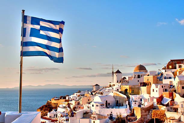greek flag over oia - oia santorini bildbanksfoton och bilder