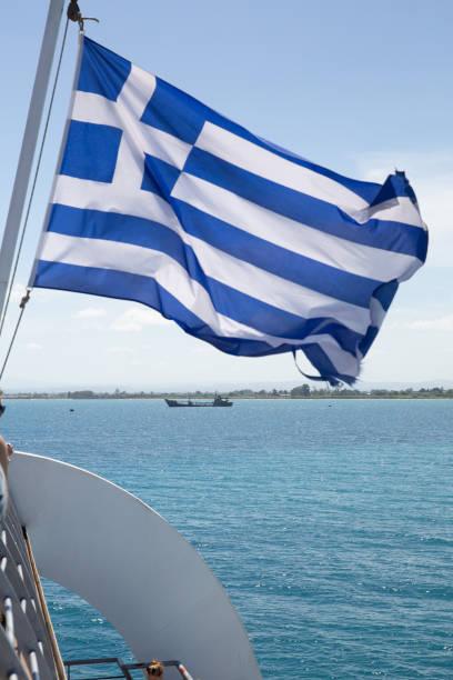 griechische Flagge weht im Wind, Himmel und Meer Hintergrund. – Foto