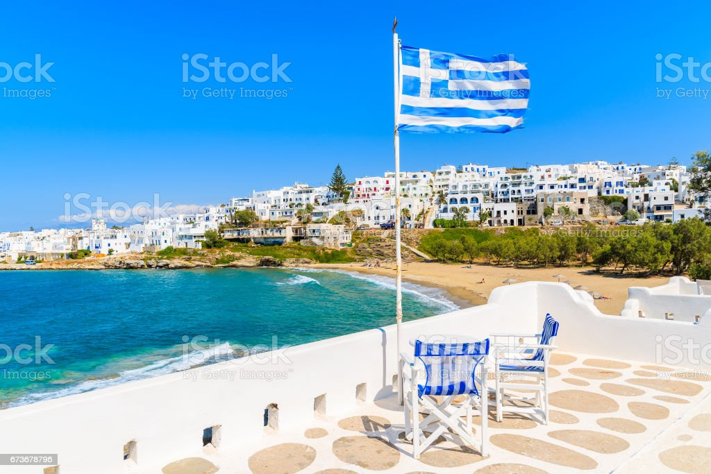 Greek flag waving on a terrace overlooking Piperi beach in Naoussa village, Paros island, Cyclades, Greece stock photo