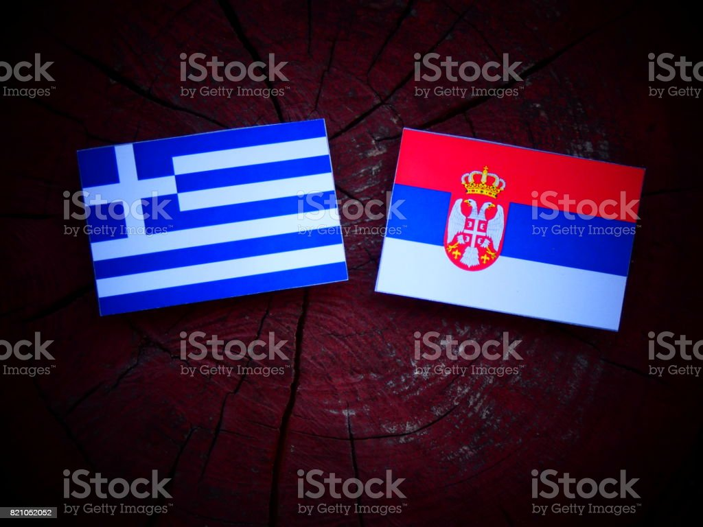 Greek flag with Serbian flag on a tree stump isolated - fotografia de stock