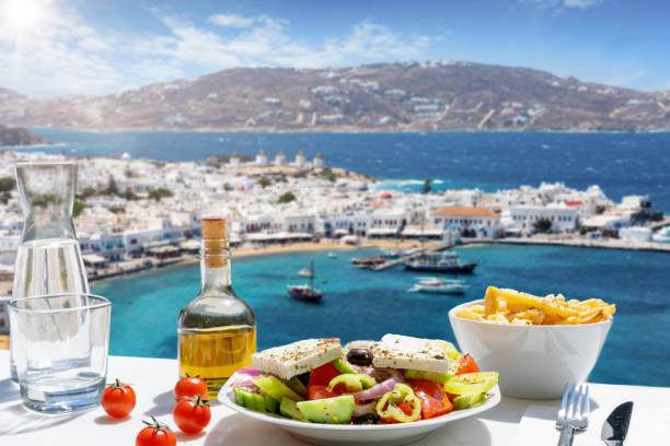 grekisk mat med sallad, fetaost och olivolja serveras med utsikt över ön mykonos - egeiska öarna bildbanksfoton och bilder