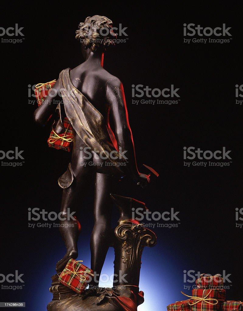Greek god figurine holding Christmas presents royalty-free stock photo
