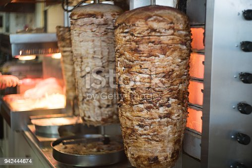 Close up shot of stacked meat roasting to be used in preparation of traditional Greek dish gyros or Turkish durum doner.