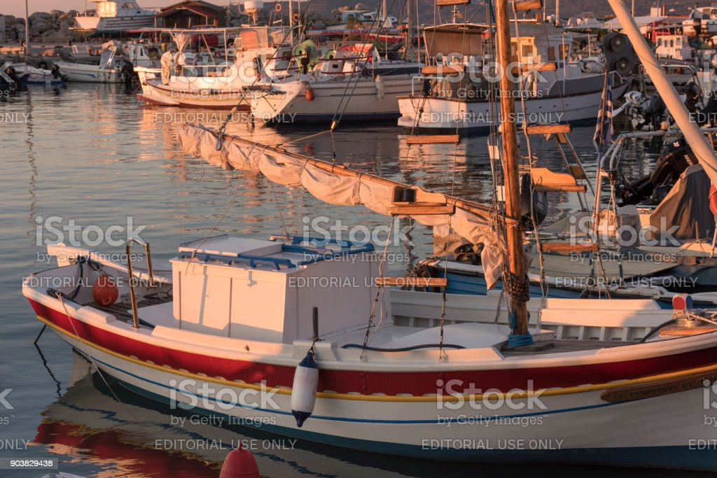 Greek Island harbor in early morning golden sunlight at sunrise stock photo