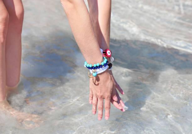 griechischen schmuck werbung am strand - armband water stock-fotos und bilder
