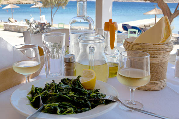 Greek khorta, white wine on restaurant table near the sea. Dodecanese Islands stock photo