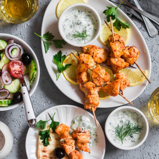 greek lunch - chicken kebabs, salad, tzatziki, flatbreads, white wine - kebab marinade stock-fotos und bilder
