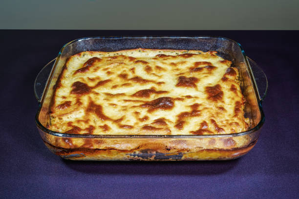 Greek moussaka dish recipe preparation. Ready meal on table at transparent bowl of baked mousaka with bechamel white sauce & fried chopped potatoes above ground chopped beef meat. stock photo