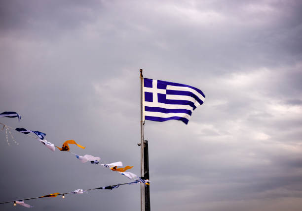 Greek national flag on flagpole and some other small flags waving against a dramatic blue sky stock photo