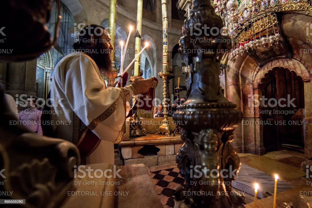 Jerusalem, Israel - July 13, 2014: Greek Orthodox priest holds mass in front of the Aedicula, place believed to be the tomb of Christ. Greek orthodox community celebrates masses every day at midnight in the Church of Holy Sepulchre in Jerusalem. All privi stock photo