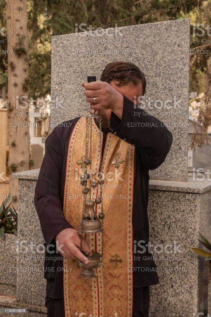 Padre ortodoxo grego que agita o incenso e que praying uma bênção no cemitério. - foto de acervo
