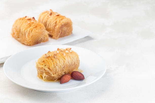 Greek pastry Kataifi with shredded filo dough stuffed with almond nuts, in honey syrup, on white plate, horizontal, copy space stock photo